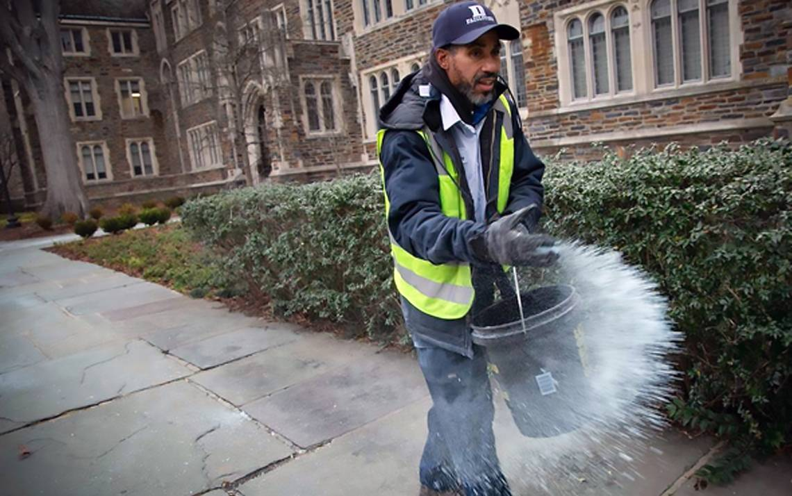 Elvis Holden, a Facilities Management Department landscape specialist, spreads ice melt in front of the Old Chemistry Building on Friday morning. Photo by Jared Lazarus/Duke Photography