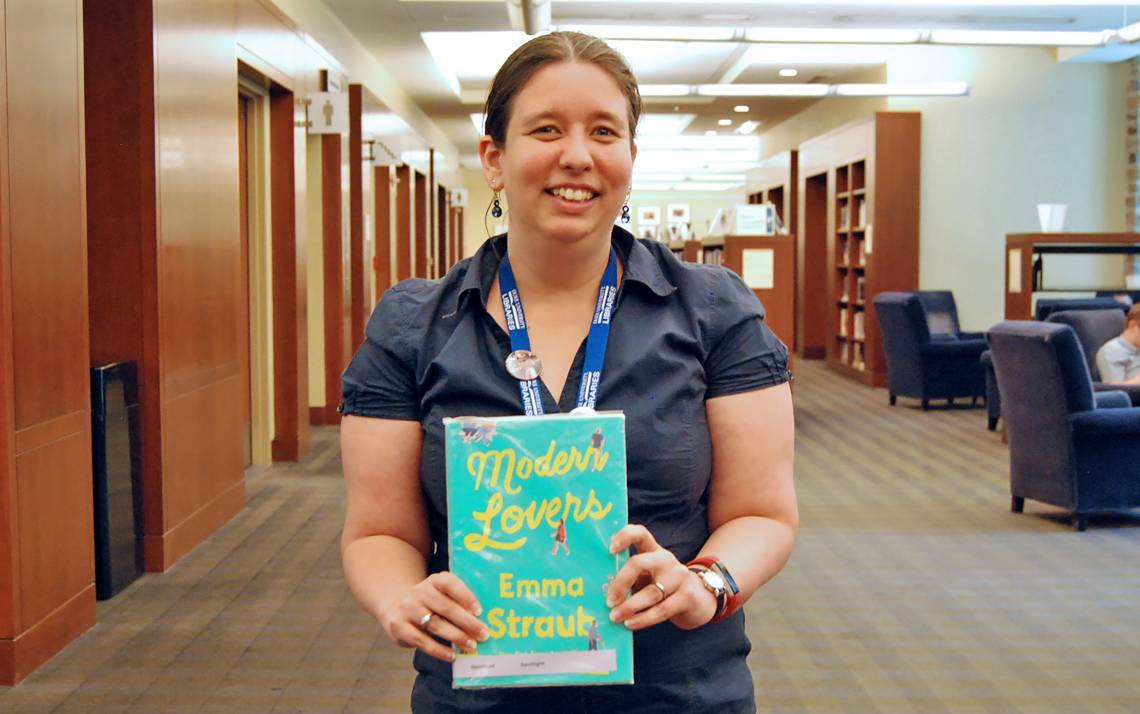 Associate Librarian Arianne Hartsell-Gundy holds one of her suggested beach reads in Perkins Library. Photo by Stephen Schramm.