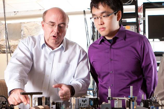 Duke Professor Warren Warren coaches a student in a laser lab