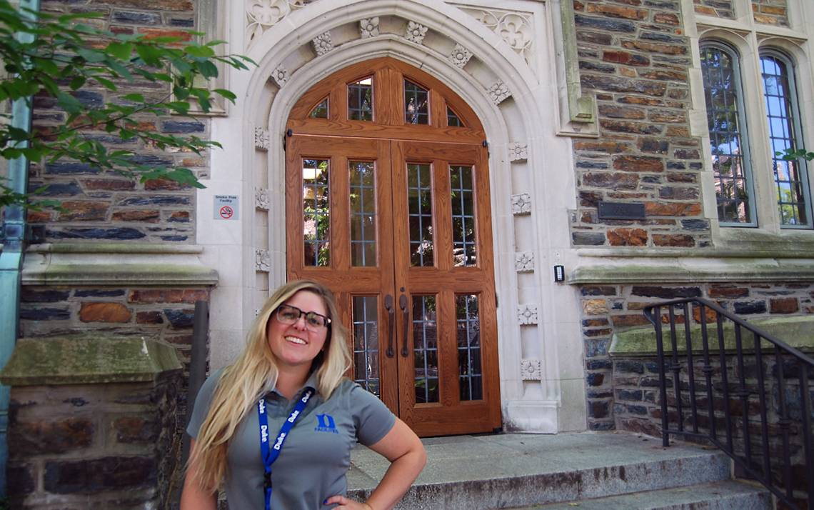 Duke Facilities Management Program Manager Belle Farish stands in front of a repaired door on the Social Sciences Building.