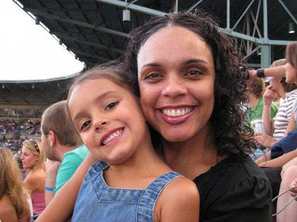Makeba Wilbourn with her daughter, Justice, at the Durham Bulls Athletic Park. Wilbourn studies children and the acquisition of knowledge.