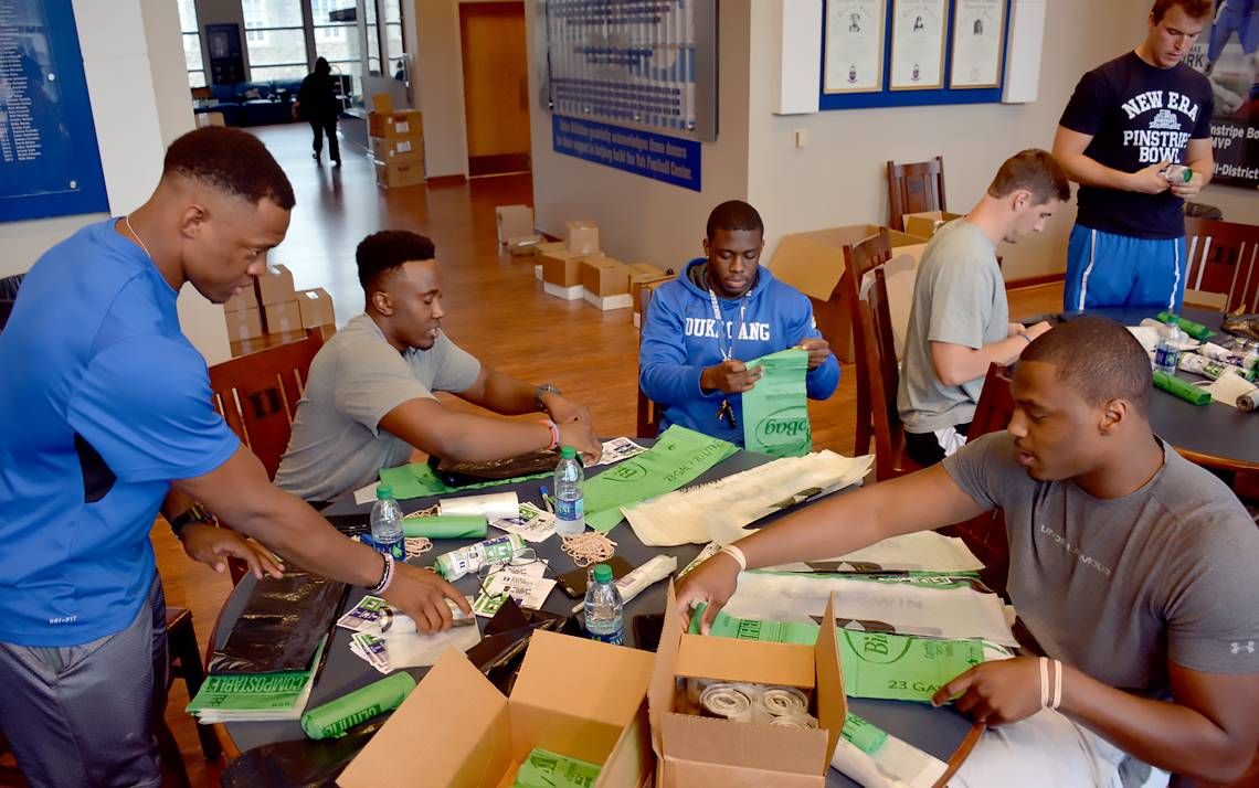From left, Duke football teammates Zavier Carmichael, Twazanga Mugala, Shaun Wilson and Trevon McSwain form an assembly line-like process to roll up bags for fans for recycling, compost and trash at Duke home games. Photo by Bryan Roth.