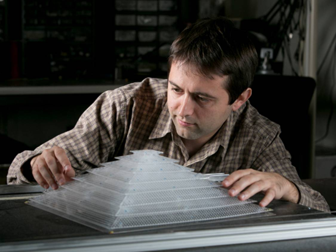 Bogdan Popa, a research scientist in electrical and computer engineering, shows off the 3D acoustic cloak he helped design and build as a member of Steven Cummer's laboratory