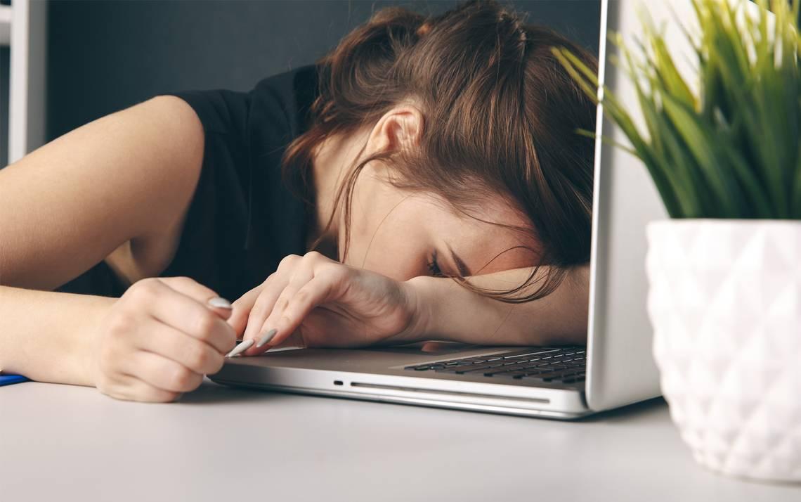 A woman asleep at her desk.