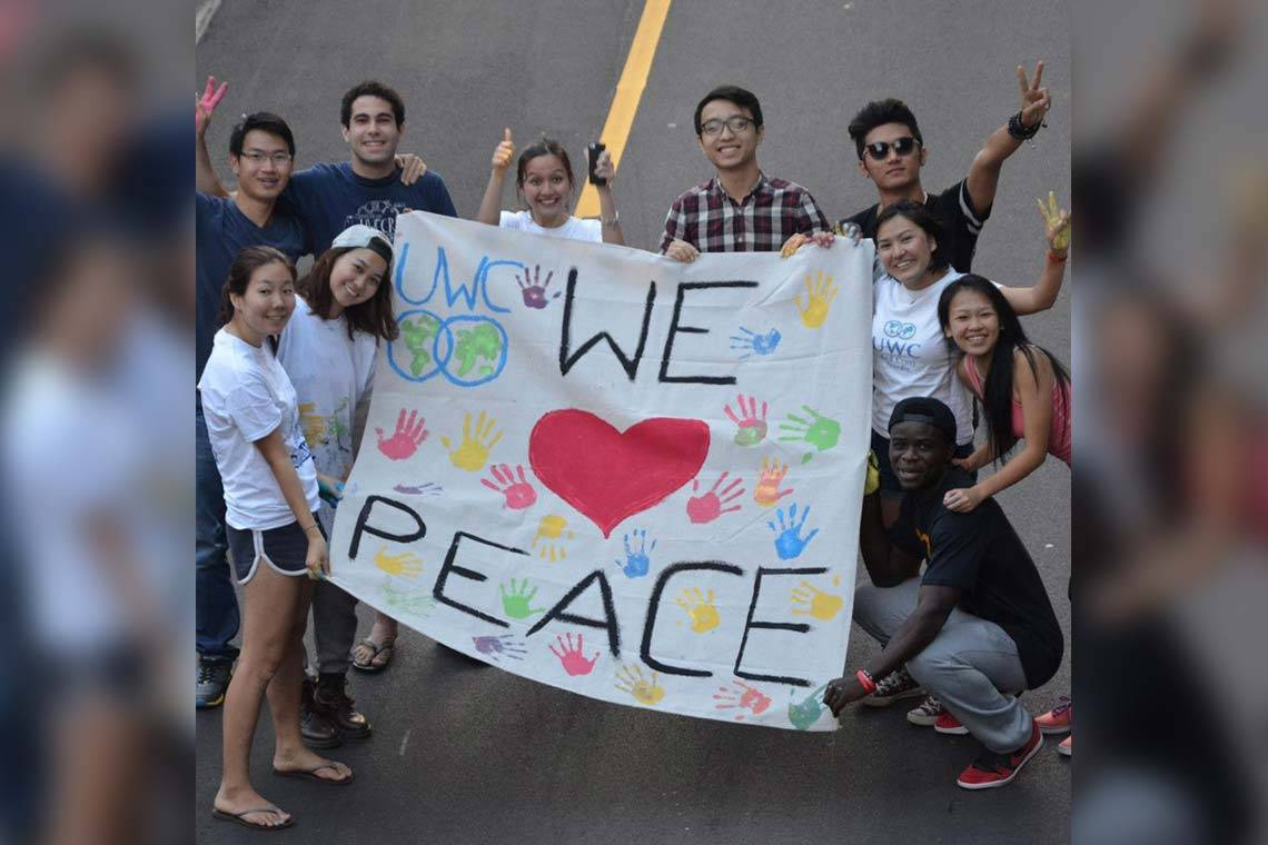 10 students from UWC schools pose with a hand-painted banner that reads 'UWC WE <3 PEACE'