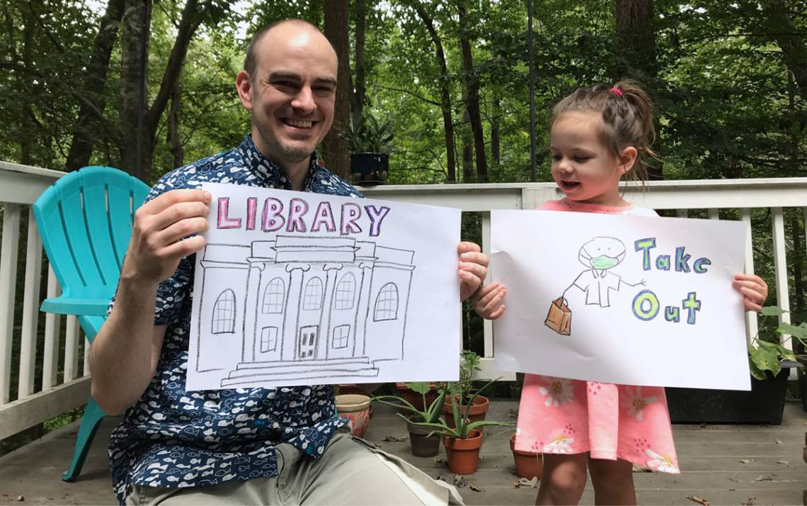 Jamie Keesecker and his daughter Naima hold up drawings used in the Library Takeout video. Photo courtesy of Jamie Keesecker.