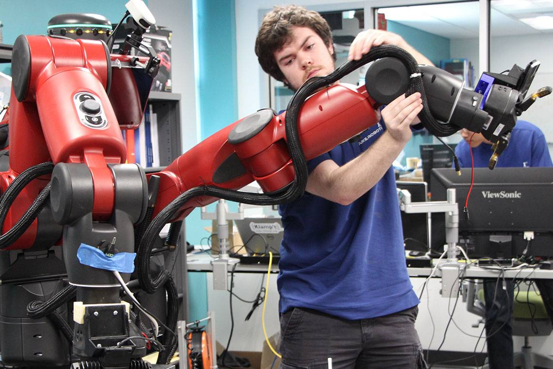 A student works on a robot arm