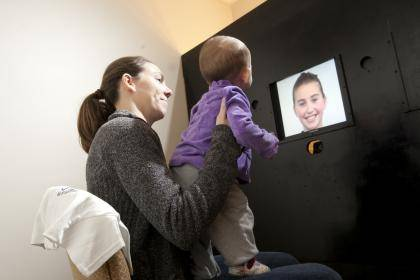 Lauren Furer and her daughter Olivia look at images on a video monitor and in a picture book as part of a study exploring how young children learn to label emotions. Photo by Les Todd
