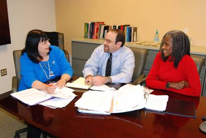Joan Podleski, left, director of the Institutional Ethics and Compliance Program, discusses clientinformation with compliance analyst Brian Lowinger, center, and assistant Sandra Reade, right.