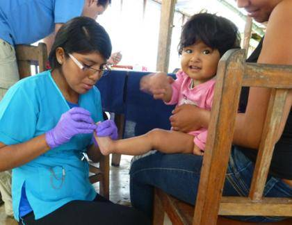 A healthcare worker collects a small blood sample from a Peruvian toddler as part of a large-scale assessment of human health around a protected area slated for mining and drilling.
