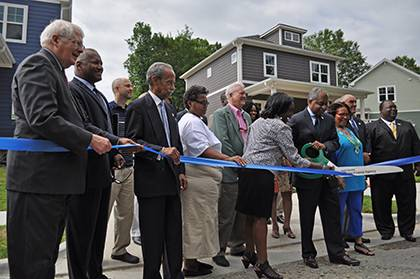 Durham Mayor Bill Bell (with the scissors), along with other local and state politicians, Phail Wynn Jr. of Duke's Office of Durham and Regional Affairs, and new Southside resident and Duke employee David Steinbrenner, attended the ribbon cutting in fron