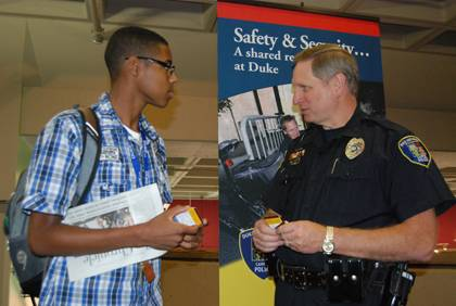 Jordan DeLoatch , left, a first-year student at Duke, talks safety with Eric Hester, crime prevention officer with the Duke University Police Department, during a