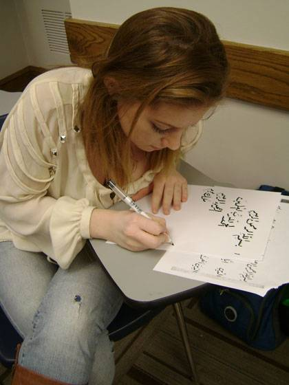 A student writes out an Arabic phrase.