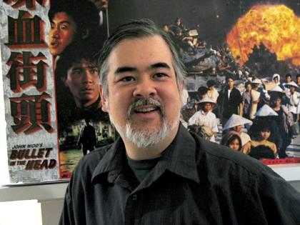 Hank Okazaki in front of a poster for a film by John Woo. Photo courtesy of Hank Okazaki.