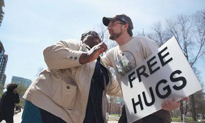 Genevieve Bien-Aime of Somerville embraced Keith Martin who advertised free hugs on Boston Commons Tuesday. Photo by Boston Globe via Getty Images.