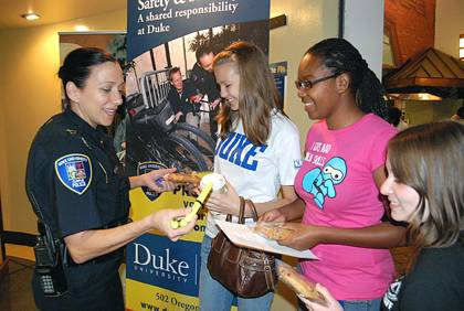 Lt. Shannan Tiffin discusses safety tips and hands out a cookie and Duke Police highlighter to first-year students. Tiffin was among DUPD officers taking part in the first