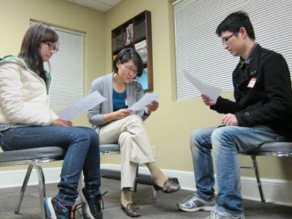 SangHee Jeong, program coordinator with the International House, center, practices her Chinese at a recent Chinese Conversation Club. It's one of sevearl weekly language and cultural learning groups offered through Duke's International House. Photo by Br