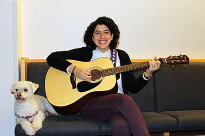 Elana Friedman poses with a guitar she keeps in her office. She's joined by her dog, Barley. Photo courtesy of Elana Friedman.