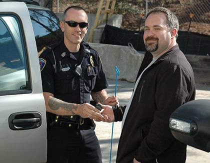 Duke lab assistant Shawn Johnson, right, serves as a Facility Watch coordinator for his building, Medical Sciences Research Building II, and is an alumnus of the Duke Police Citizens' Police Academy. In this photo, he poses as a locked-out motorist recei