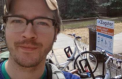 Graduate student Gabriel Yapuncich poses for a selfie by a rack of bikes with Duke's bike-share program, Zagster, as part of a social media activity for the Unpark Yourself Challenge. Yapuncich is among several employees and graduate students fighting fo