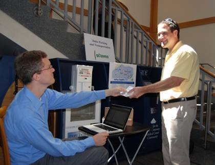 Daniel James, right, receives his free GoPass from Brian Williams, Duke's transportation demand management coordinator. Photo by Marsha A. Green.