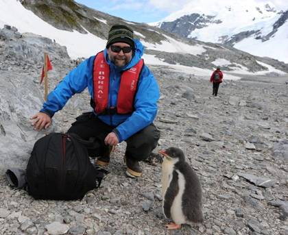 David Johnston, a research scientist with Duke's Division of Marine Science and Conservation, crouches next to a Gentoo penguin at Cuverville Island on the Western Antarctic Peninsula. Photo courtesy of David Johnston.