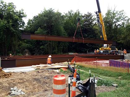 Crews worked to set large, steel beams along the West Main Street bridge in August. Construction of the bridge was one of many roadwork projects seen around campus this summer. Photo by Bryan Roth.