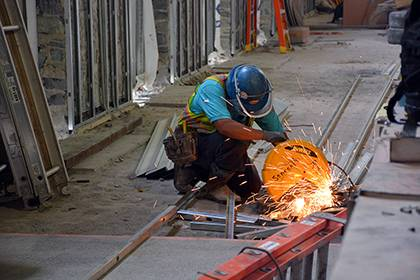 Sparks fly as a construction worker cuts through metal poles inside the West Union. The renovated space is set to open two portions of the building in February. Photo by Bryan Roth.