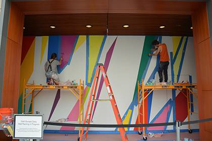 Painting assistants work on the Odita mural at the entrance of the Nancy A. Nasher and David J. Haemisegger Family Lecture Hall in Nasher. Photo by April Dudash.