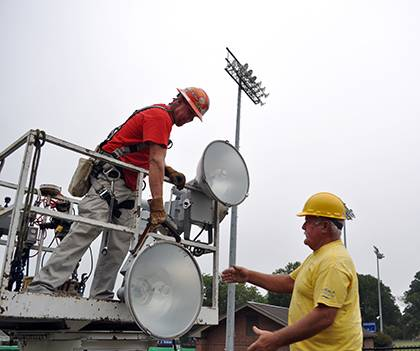 Tommy Lawrence Electrical Contractors Scott Lawrence, left, and Chuck Hayes handle new LED lights during last week's installation at Williams Field. In all, six poles were outfitted with 16 new lights each which will provide brighter illumination on th