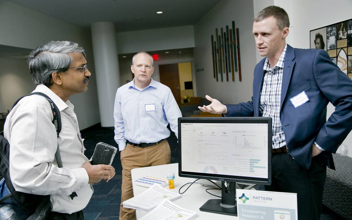 Pankaj Agarwal, far left, a database analyst in Duke Surgical Sciences, speaks with Tim Horan, center, and Ed Barber of Pattern Health, during the Mobile App Gateway kickoff at Duke.
