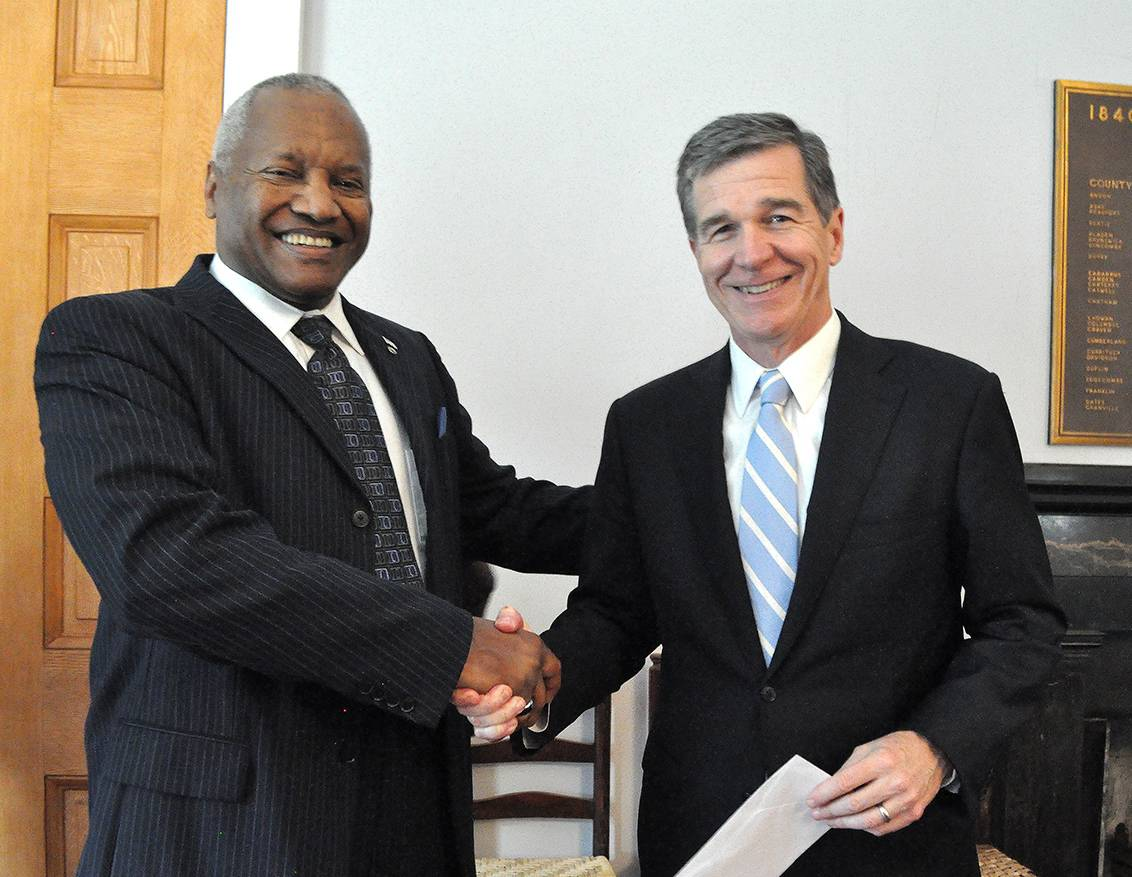 Phail Wynn presents Gov. Roy Cooper with the Doing Good check. Photo by April Dudash.