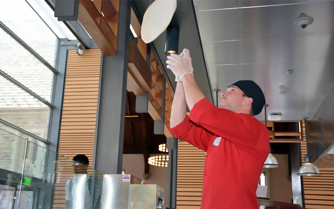 Kyle Rosch, director of operations for Duke Dining's Il Forno in the West Union, tosses dough. Photo by Beth Hatcher.