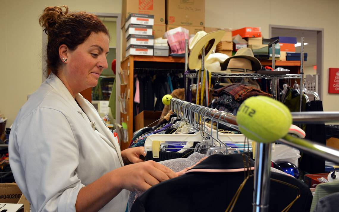 Sarah Walker, a manager at the Nearly New Shoppe, sorts through recently donated shirts and coats. The store, which supports medical and nursing scholarships, is seeking additional donations in the next two weeks.