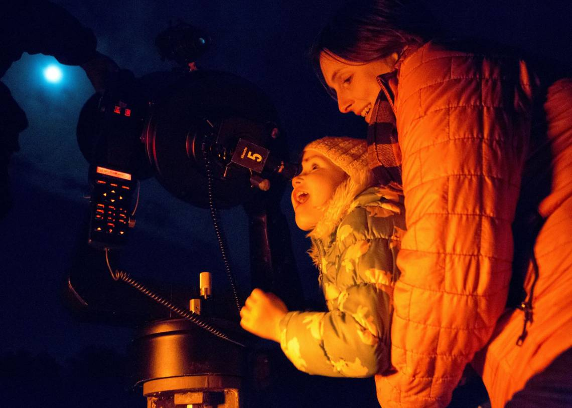 Maura Farver of Durham holds Poppy Overman, 3, in awe as she views the moon's craters through a telescope at the Duke Teaching Observatory in Duke Forest. Photo by Jared Lazarus, Duke University.