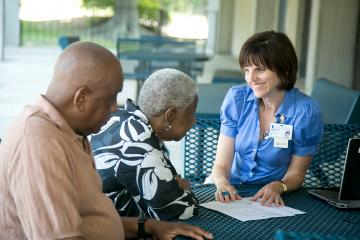 Dr. Teah Bayless talks with an elderly couple