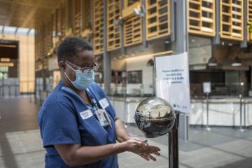 Housekeeper Beverly Jordan uses the hand sanitizer at the entrance to the Brodhead Center, where visitors are encouraged to wash their hands as part of Duke University's response to the COVID-19 pandemic.