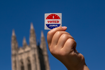 Duke student shows I Voted sticker on Duke's campus