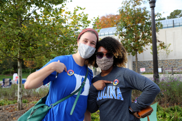 Early voting at Duke can even bring rivals together. Meredith Rawls, a Duke Divinity School student, poses after voting with UNC social work student Nikki Moore.