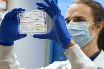 photo of lab worker checking test vials