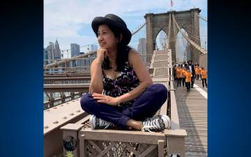April Ferido poses on a railing in the middle of the Brooklyn Bridge. Photo courtesy of April Ferido.