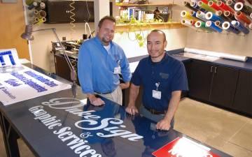 Two men int he Duke Sign Shop.
