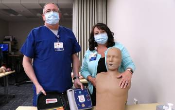 Tracy Stell and Brittany Hill pose with a dummy used during Basic Life Support Training. ​Hill's recertification course helped her feel confident enough to perform CPR on an accident victim.
