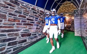 Duke football players walk to the field.