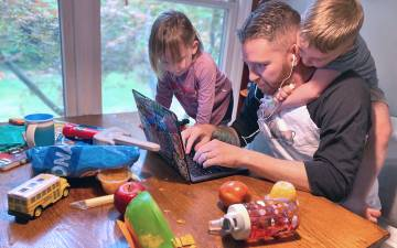 Kyle Fox working at his laptop with his children.