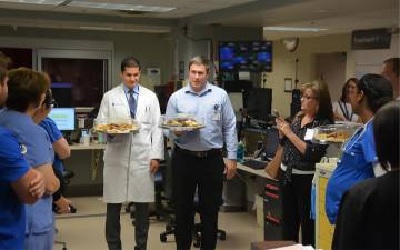 Neurosurgeons John Barr, left, and Steven Cook, right, hand out baked goods and thank you cards to employees at Duke Regional Hospital's Emergency Department. Photos by Jonathan Black.