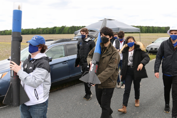 Duke mechanical engineering undergraduates approach the launch site carrying Thing 1 and Thing 2, the two stages of the rocket they successfully launched at Bayboro, N.C., April 25.