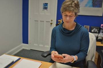 Mary Greenway, executive assistant to Provost Sally Kornbluth, works from her cellphone in her office in February. Photo by Jonathan Black.