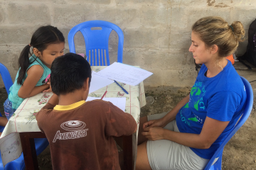 Duke researcher Helena Frischtak, (right front) administers psycholocal assements with a pair of Peruvian children during a study of mercury contamination near small-scale gold mining. (Bill Pan, Duke)