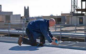 Electrician Bob Moffett repairs a light on top of Duke University Hospital. Photo by Stephen Schramm.
